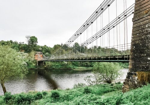 Spencer Group to begin rebuild of historic chain suspension bridge cover image